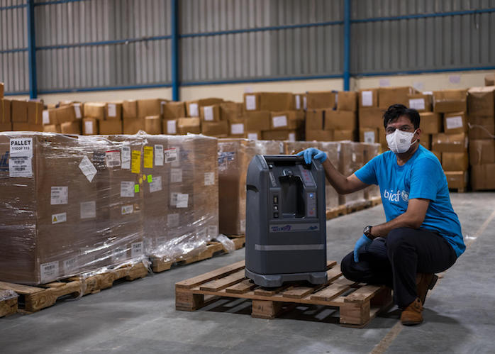 A UNICEF worker examines a shipment of oxygen concentrators at a warehouse in Delhi, India.