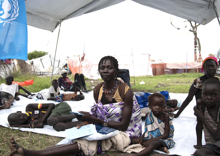 Nyachimach and her eight children have been displaced four times by conflict and flooding in South Sudan, Here, they wait outside a UNICEF-suported health facility in Pibor.