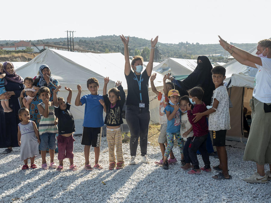 UNICEF staff lead children in a game outside a temporary facility for refugees and migrants on the Greek island of Lesvos.