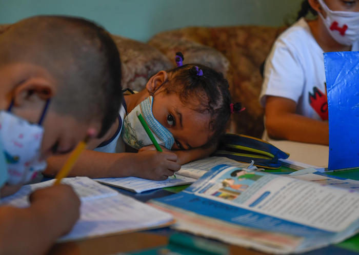 On 16 September 2020, children attend class in an improvised classroom in a house in Petare neighbourhood, Venezuela's largest slum, in Caracas, amid the COVID-19 pandemic.