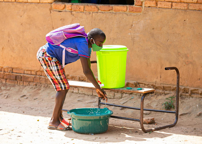 Lovewell, 17, washes hands after attending classes at UNICEF-supported Luwambaza primary school in Malawi in 2020.