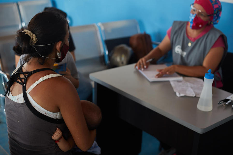 A woman and her sons attend the Integral Care Center for Children, Adolescents and Women (CAINAM) to receive comprehensive care after returning to the country, in the San Antonio bus terminal in Táchira, Venezuela, on August 19, 2020.