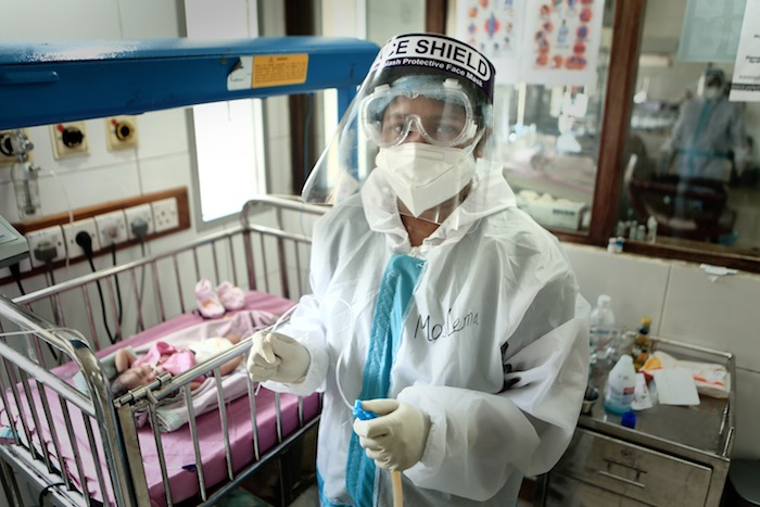Nurse wearing a PPE getting ready to clean a baby's nose inside the NICU. This photo was taken on 09 May 2020 at BSMMU in Dhaka, Bangladesh.