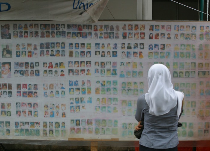 In Indonesia in 2005, a woman searches for her missing child on a board showing photos of children who have become separated from their families.