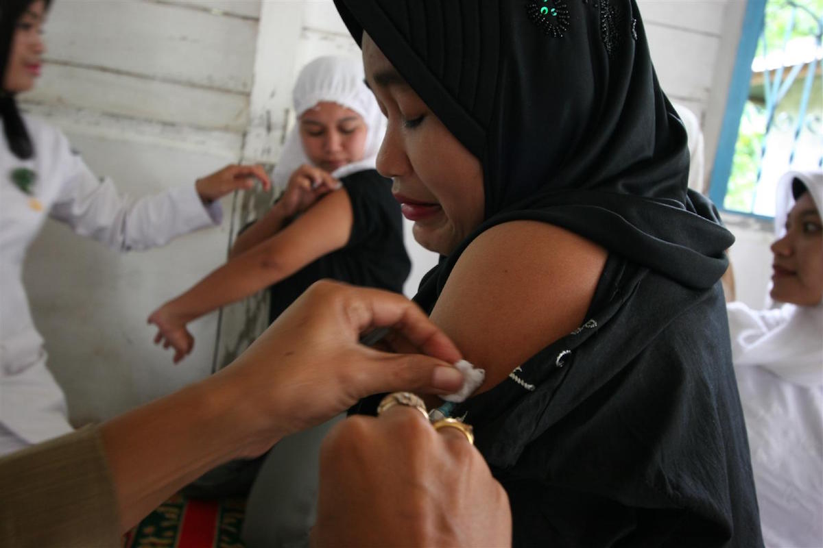 A woman's arm is swabbed by a health worker following a tetanus vaccination in the village of Semeureung, Indonesia. © UNICEF/Estey