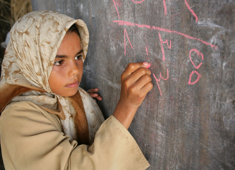 A girl writes on the blackboard during an arithmetic lesson at a local primary school in Yemen 2007.