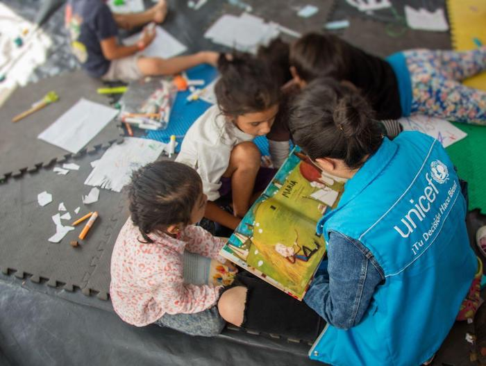 UNICEF's strategy for providing mental health and psychosocial support to migrant children includes creating safe spaces for children to learn and play.