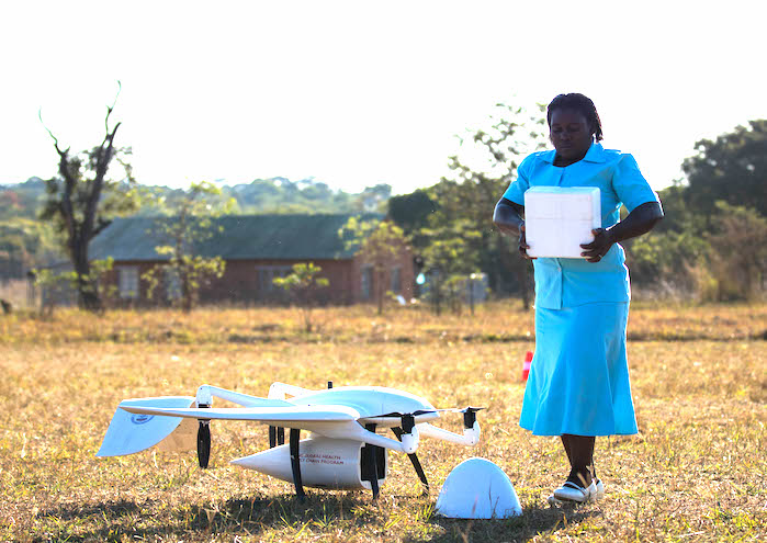 UNICEF-supported community health worker Elizabeth Pemba with the lifesaving drone cargo near the Lifupa health center in Malawi.