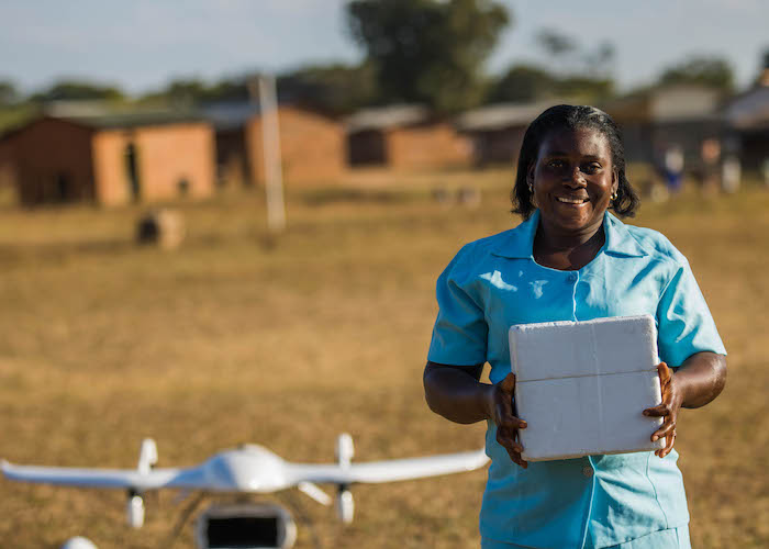 Community health worker Elizabeth Pemba holds lifesaving medical supplies delivered by UNICEF-supported drone in Malawi in 2019.