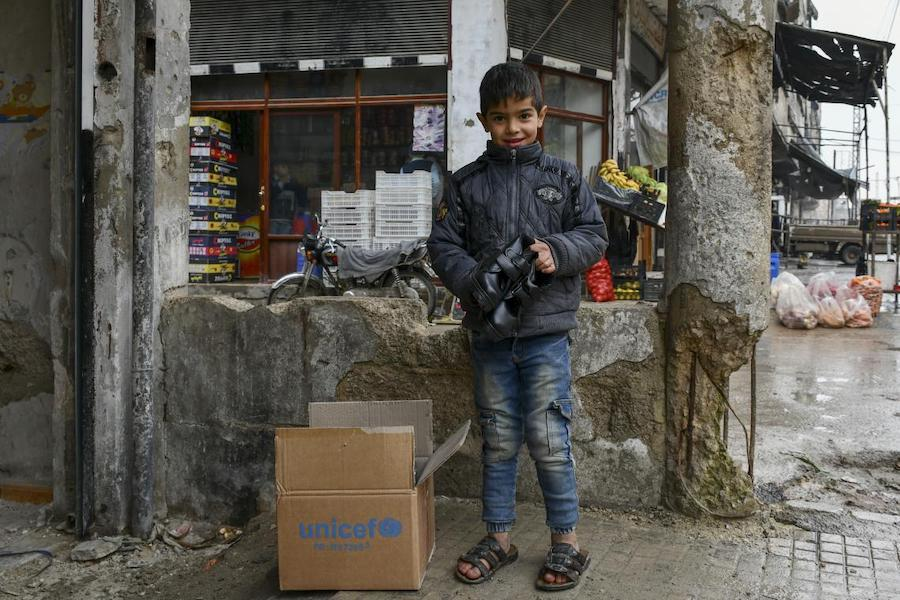 "Amjad, 8, happily checks the new shoes he received as part of the winter clothing kit distributed by UNICEF in Hammourieh, rural Damascus, thanks to a generous contribution from Canada and DFID. ""I only have slippers, so my feet are always wet which makes"