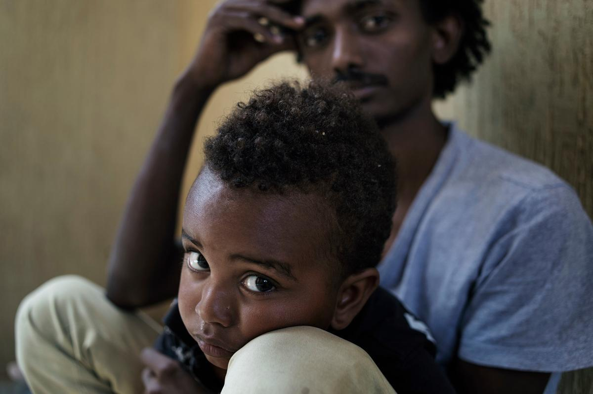 A young father and son at Alguaiha detention center for illegal migrants in Garabulli, Libya.