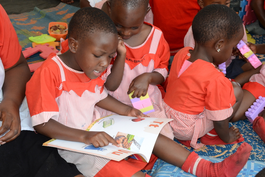 Children read and write in a tent set up during a UNICEF Early Childhood Development activation in the stadium of Kabale Municipality in South Western Uganda on February 2, 2017.