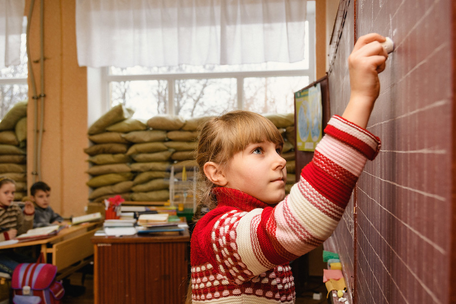 Fourth grader Angelina, 10, writes on a blackboard at School No. 2, Marinka, Ukraine, January 2017. Sandbags reinforce the windows to prevent them from shattering during frequent shelling.