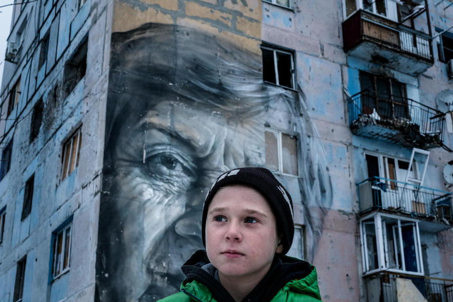 "Vadim, 9, stands outside his old home in a building known by locals as the ""coloring book,"" in Avdiivka, Donetsk Oblast, Ukraine. When he was six, he was injured by shelling, and when he was seven, he was run over by a Ukrainian military vehicle."