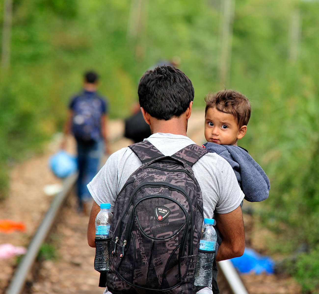 A father holds a young son while he walks the long road through Macedonia. Donation Form Background