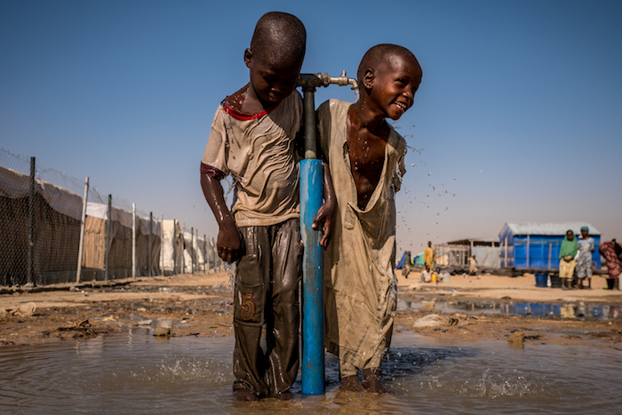 Children play at a water tap during recess at a UNICEF-supported primary school inside Bukasi Internally Displaced People's camp in Maiduguri, Borno State, Nigeria in February 2017.