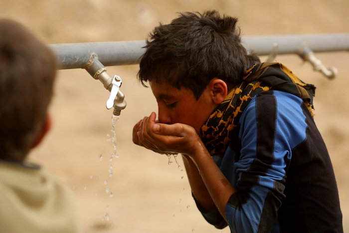 Syrian refugee Mohammad, 13, drinks from a tap installed by UNICEF in Karama camp, rural Ar-Raqqa, Syria.