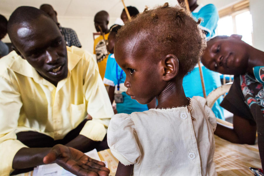 A nutrition officer tries to engage 2-year-old Maria, who has been diagnosed with severe acute malnutriton, at a UNICEF-supported hospital in Juba, South Sudan in October 2017.