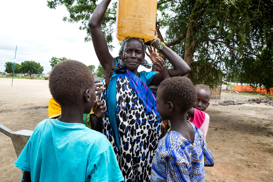 Angelina Nyakuma is surrounded by her children as she carries a jerry can of safe drinking water, drawn from a water pump at the Machakos Primary School, Bentiu, South Sudan, July 2017.