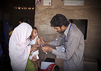 A health worker examines a child in Suleman Kehari village in southern Sindh Province, Pakistan.| © UNICEF Pakistan/2011