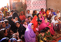 Women and children listen to a health education session in Pakistan