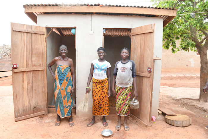 Two young girls with their grandmother in front of their new latrine in the village of Dibobly, Côte d'Ivoire.