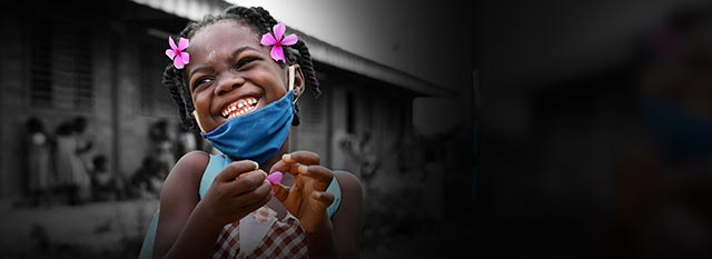 A girl wearing a face mask smiles in front of her school