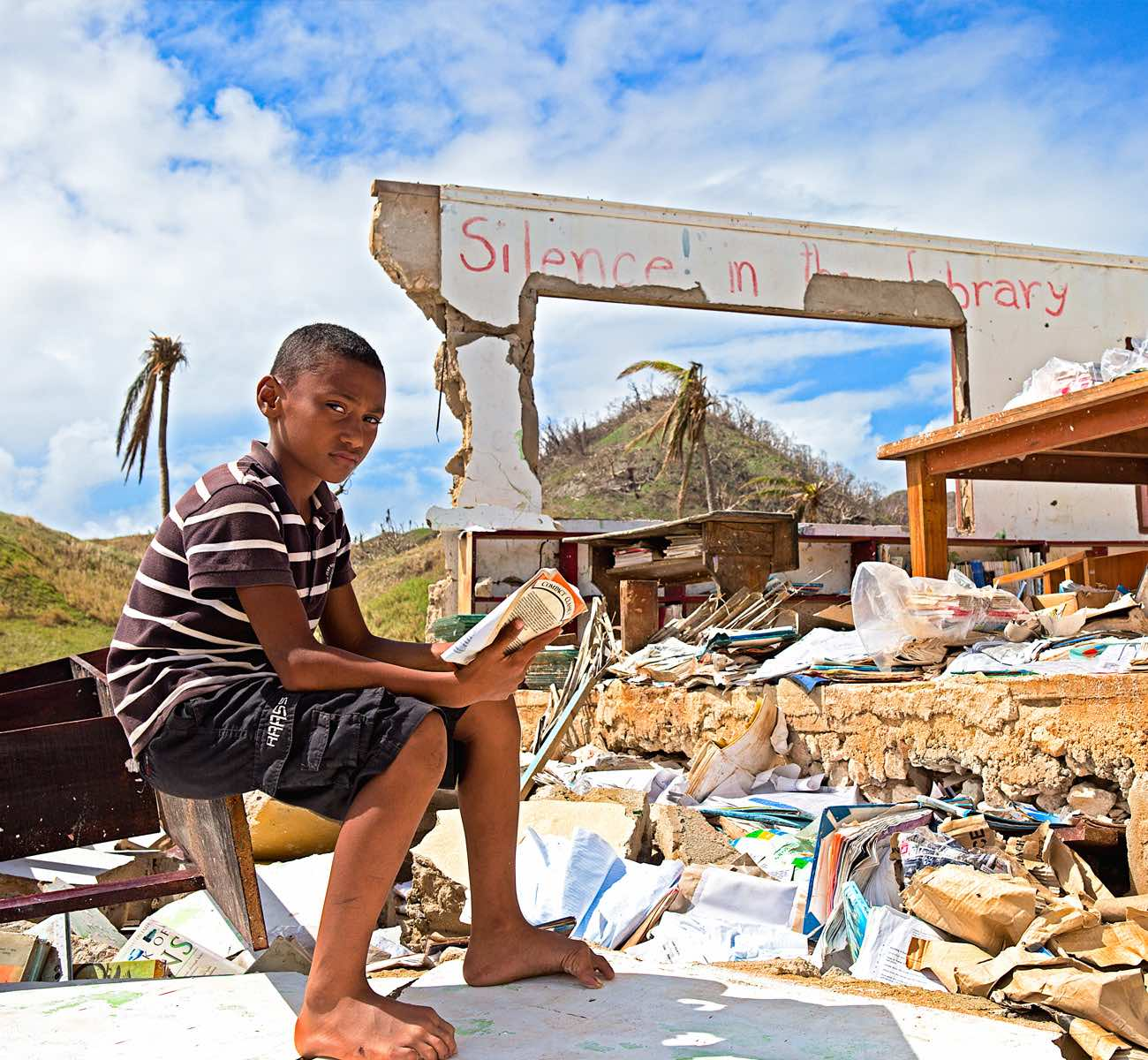 Amid the rubble of a collapsed library, a boy from Vanuatu sits in one of the library's exposed chairs and reads a book from its sun-drenched shelves.