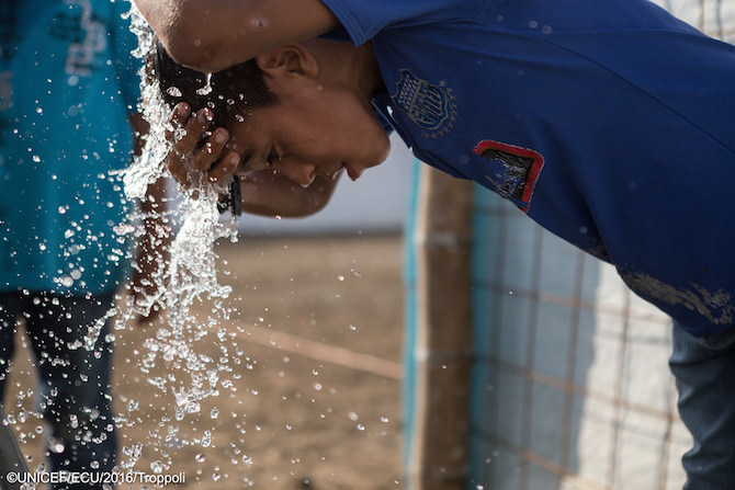 A child splashes at a UNICEF-installed tap at a ETEP in Manabi, Ecuador.