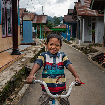 a smiling boy rides his bicycle
