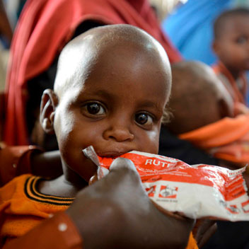 a boy eats with his mouth on the open end of a fruit product wrapper