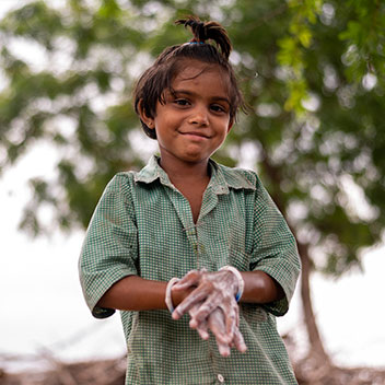 a smiling boy standing outside washes his hands with soap