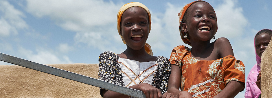 At a displacement camp in Garin Wazam, Niger, two girls pump water from a new borehole installed by UNICEF and partners.