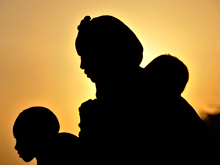 A woman and two children are silhouetted by the rising sun as they wait to register for aid in an area for new arrivals, in the Ifo camp for Somali refugees in North Eastern Province, near the Kenya-Somalia border. Kenya 2011