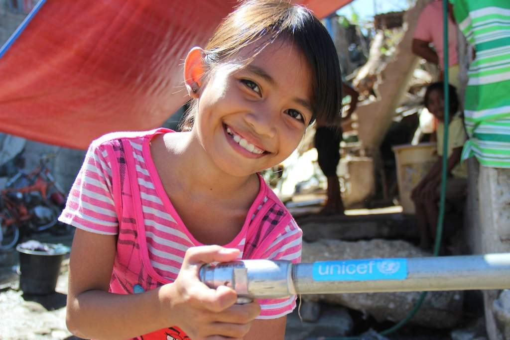 Residents of Rawis, in the Philippines, suffer hardship during typhoon season. Cherlyn, 9, recalls sheltering at school, where there is a water pump provided by UNICEF.