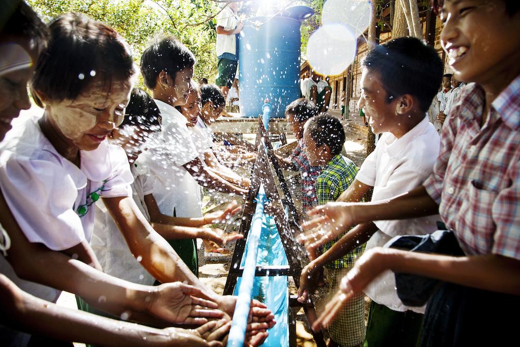 Fourth graders from Hnen Ser Kyin Middle School in Myanmar wash their hands at a community water point set up by UNICEF and the country's Department of Rural Development.