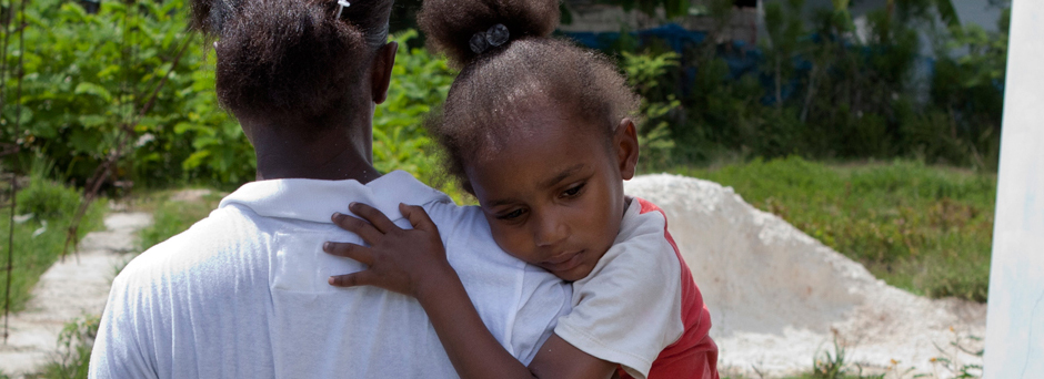 Haiti 2011. Carline, 4, is carried by her mother, who walks through the town of Léogâne, Ouest Department.