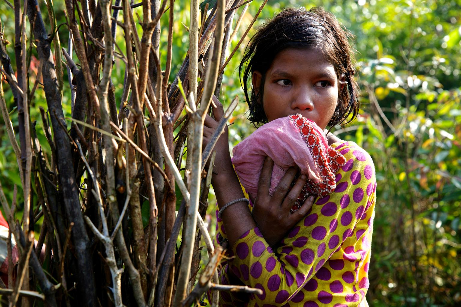 In Bangladesh, Sabiha, 11, takes a break from chopping kindling for her family,far from their shelter in a Balukhali makeshift settlement for Rohingya refugees.