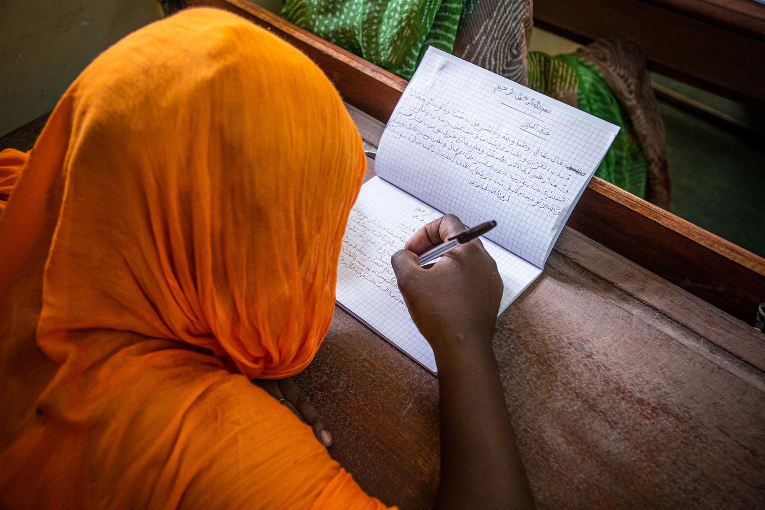 A young girl takes notes during an Arabic language class at a center for girls who are victims of gender-based violence.