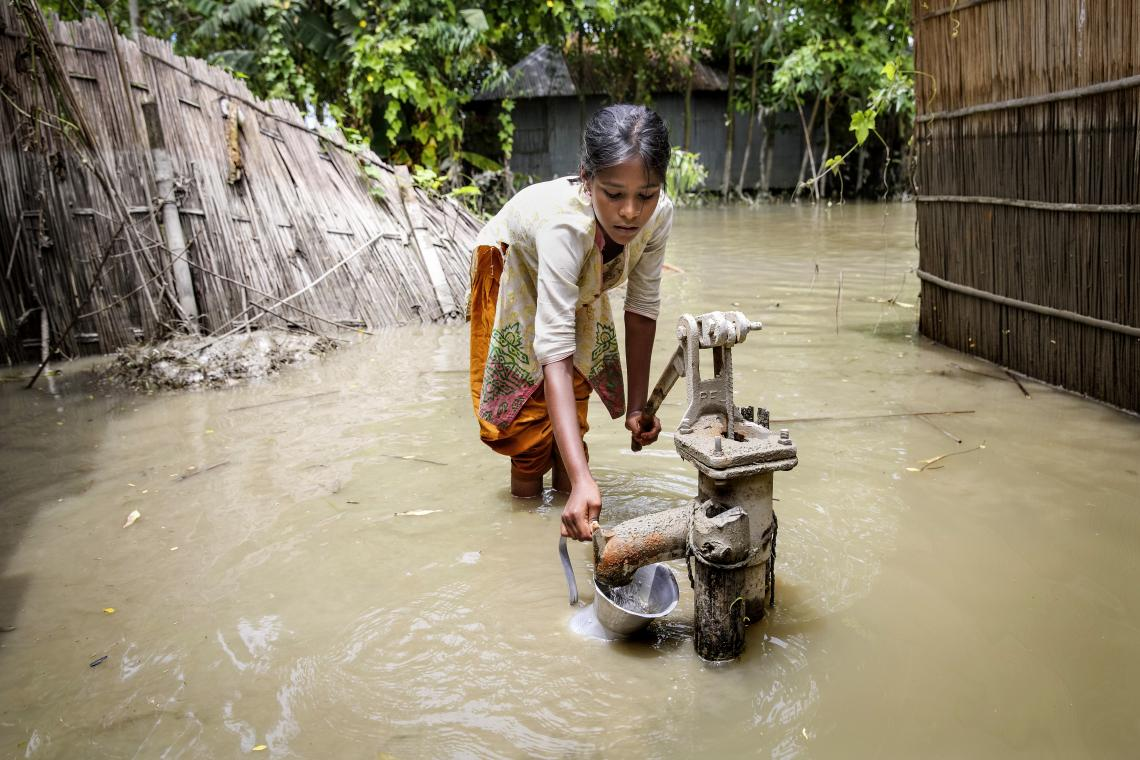 During the 2016 floods in Kurigram, northern Bangladesh, a girl tries to pump clean water from a standpipe. The contamination of drinking water supplies is a major risk during flooding.
