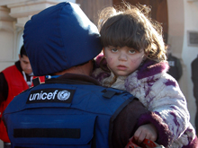 Girl being carried by a UNICEF man looks at the camera