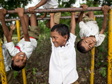 Children play during their lunch break at The Zilla Parishad Primary School in Muhammadpur Village. Two children are upside down on the monkey bars.