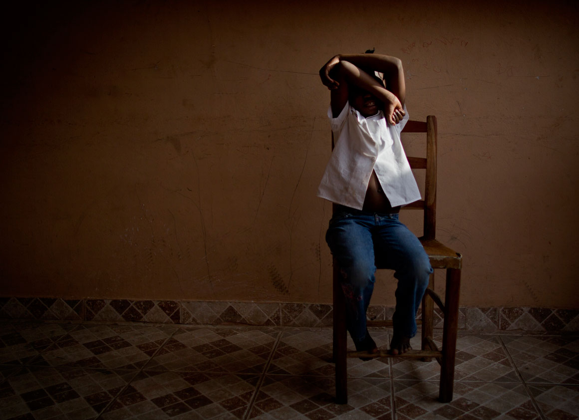 [NAMES CHANGED] Eight-year-old Marie hides her face in a dormitory in the Dominican Republic.