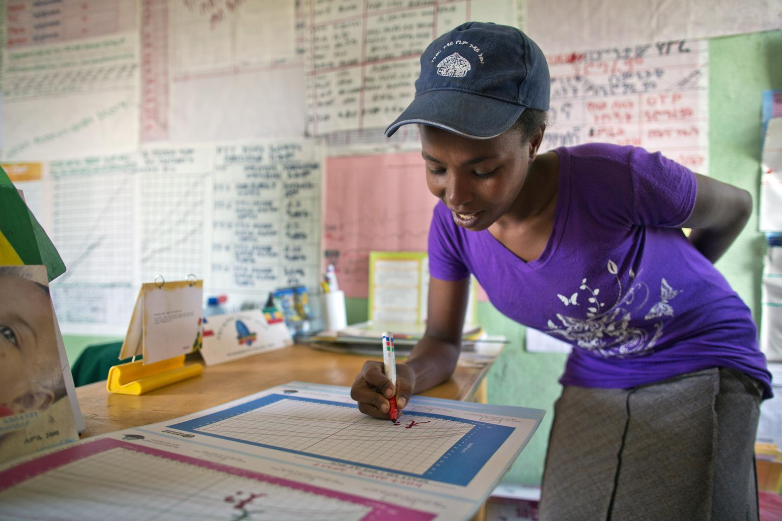 Salemwoit Negase, a Health Extension Worker, updates a chart at Galeto Health Post in SNNPR State of Ethiopia on April 2, 2013. Photo by Jiro Ose.