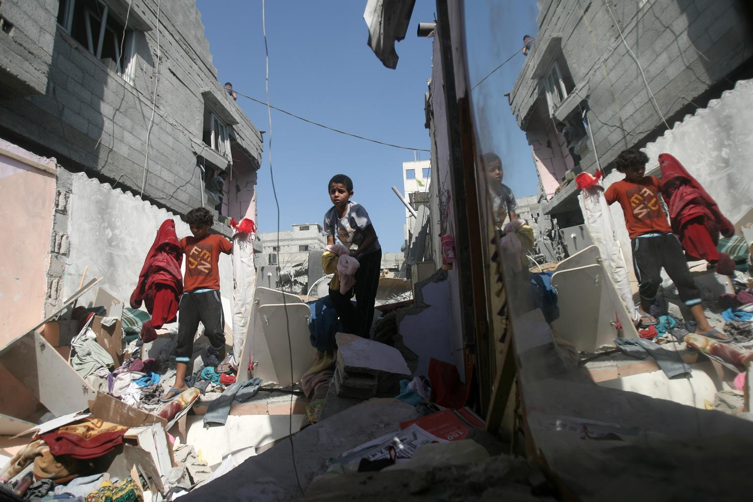 On 10 July 2014, boys carry clothing salvaged from the rubble of the Al Haj home, which was destroyed during an early morning Israeli air strike in the Khan Yunis refugee camp in the southern Gaza Strip. © UNICEF/NYHQ2014-0905/El Baba