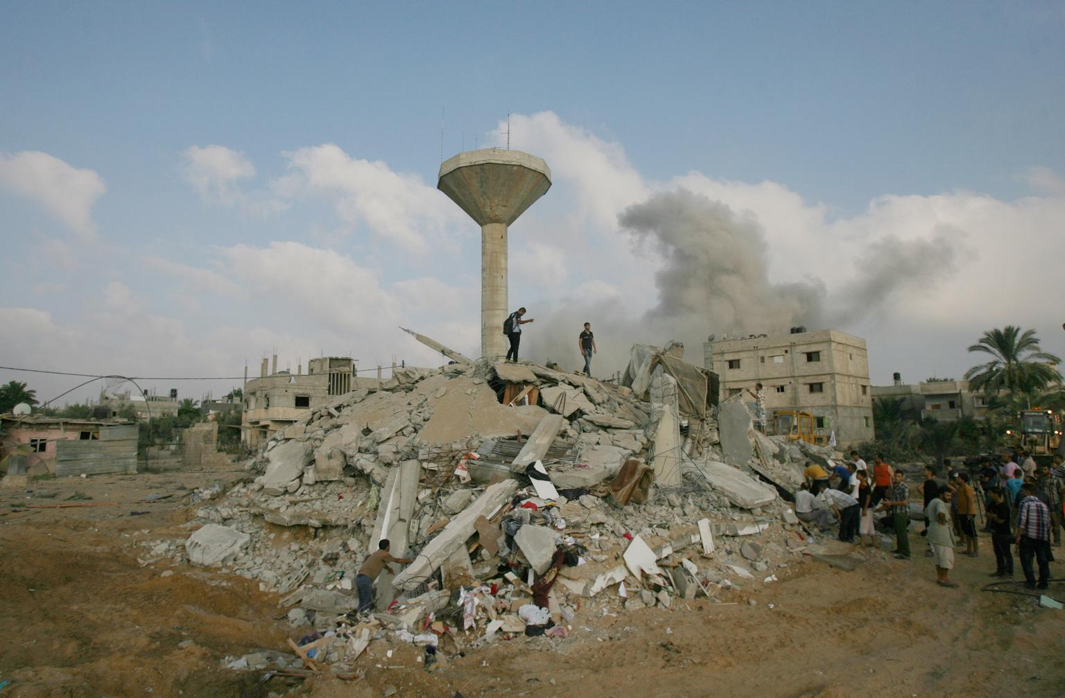 People search for victims amid the rubble of a destroyed home in the town of Rafah, southern Gaza. A cloud of smoke is visible in the distance. © UNICEF/NYHQ2014-1045/El Baba