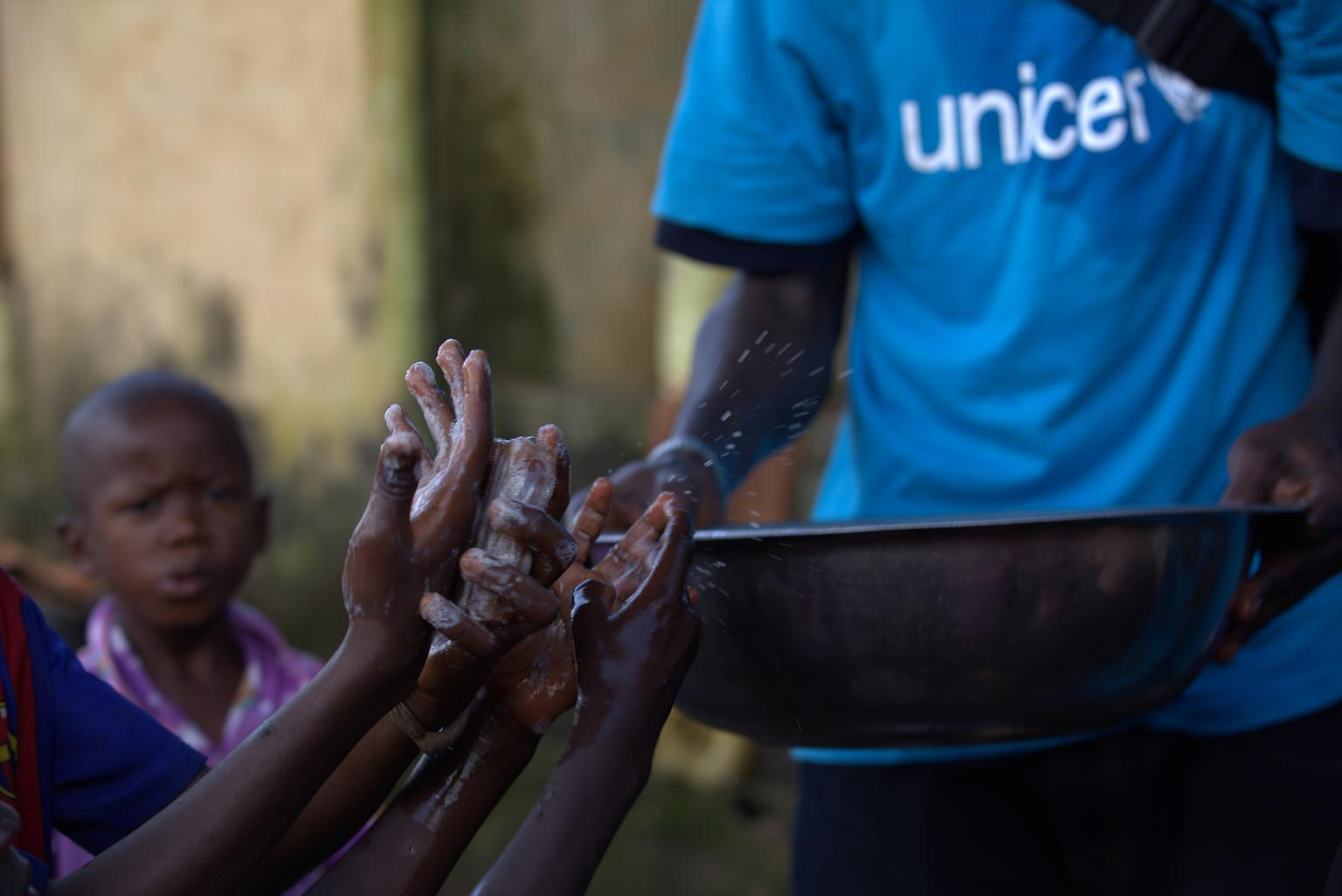 A social mobilizer from AJCOM, a UNICEF NGO partner, carries a basin of water past the soapy hands of children in Conakry, Guinea. © UNICEF/NYHQ2014-1522/La Rose
