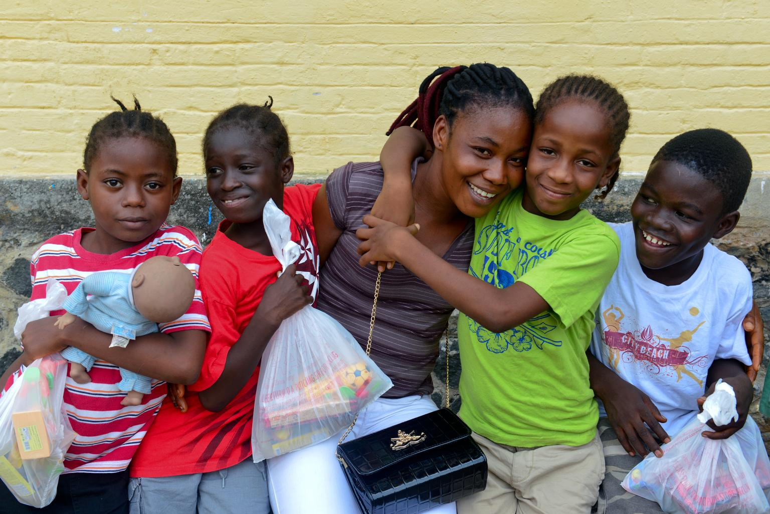 Caretaker Helen Morris hugs young children goodbye as they await being driven to foster homes or the homes of extended family members, at an interim care center for children exposed to the Ebola virus, in Monrovia, Liberia.