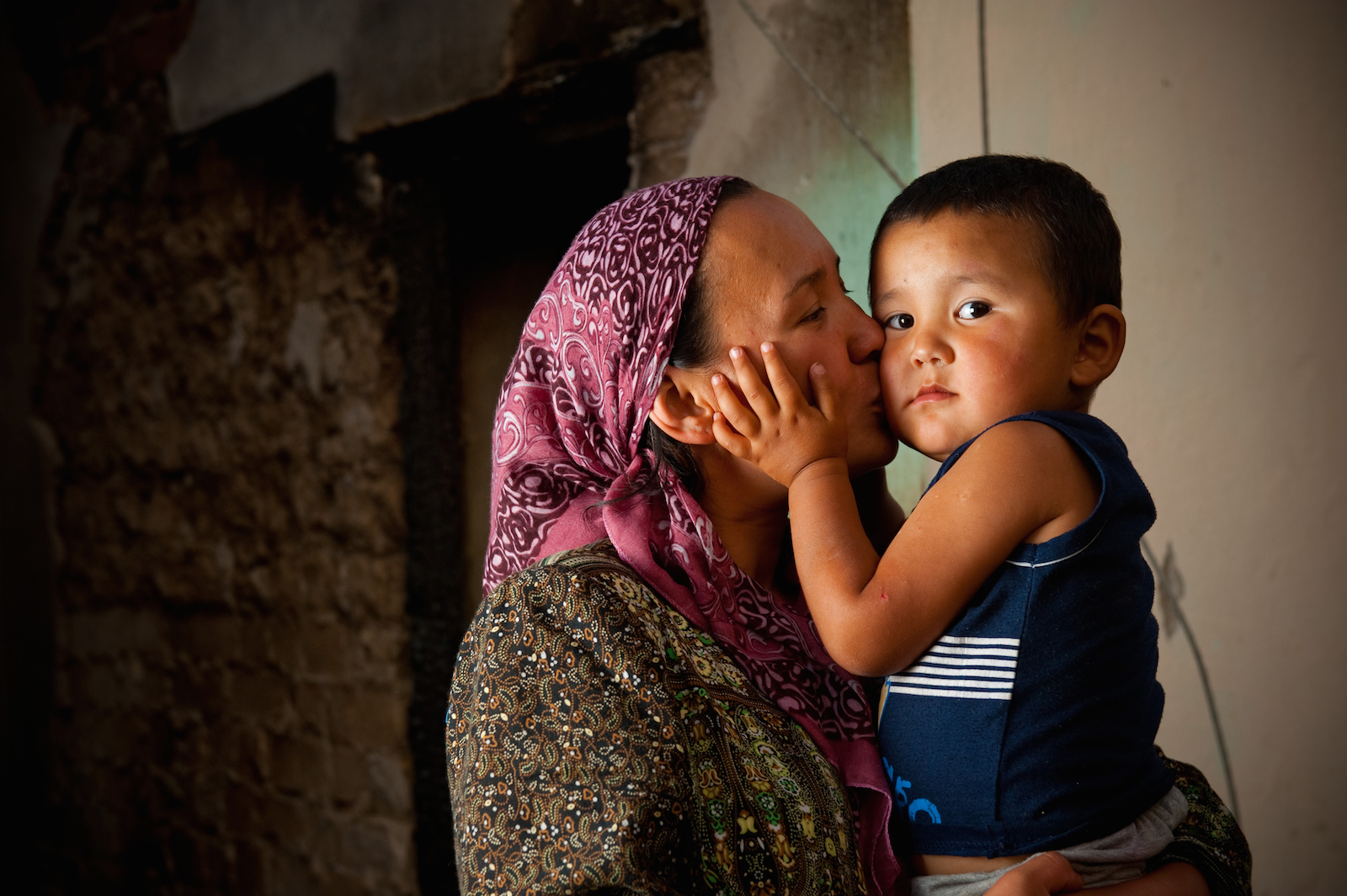 Zulhumar Amanbaev kisses her three-year-old son, Abdulmutalib, in Kyrgyzstan