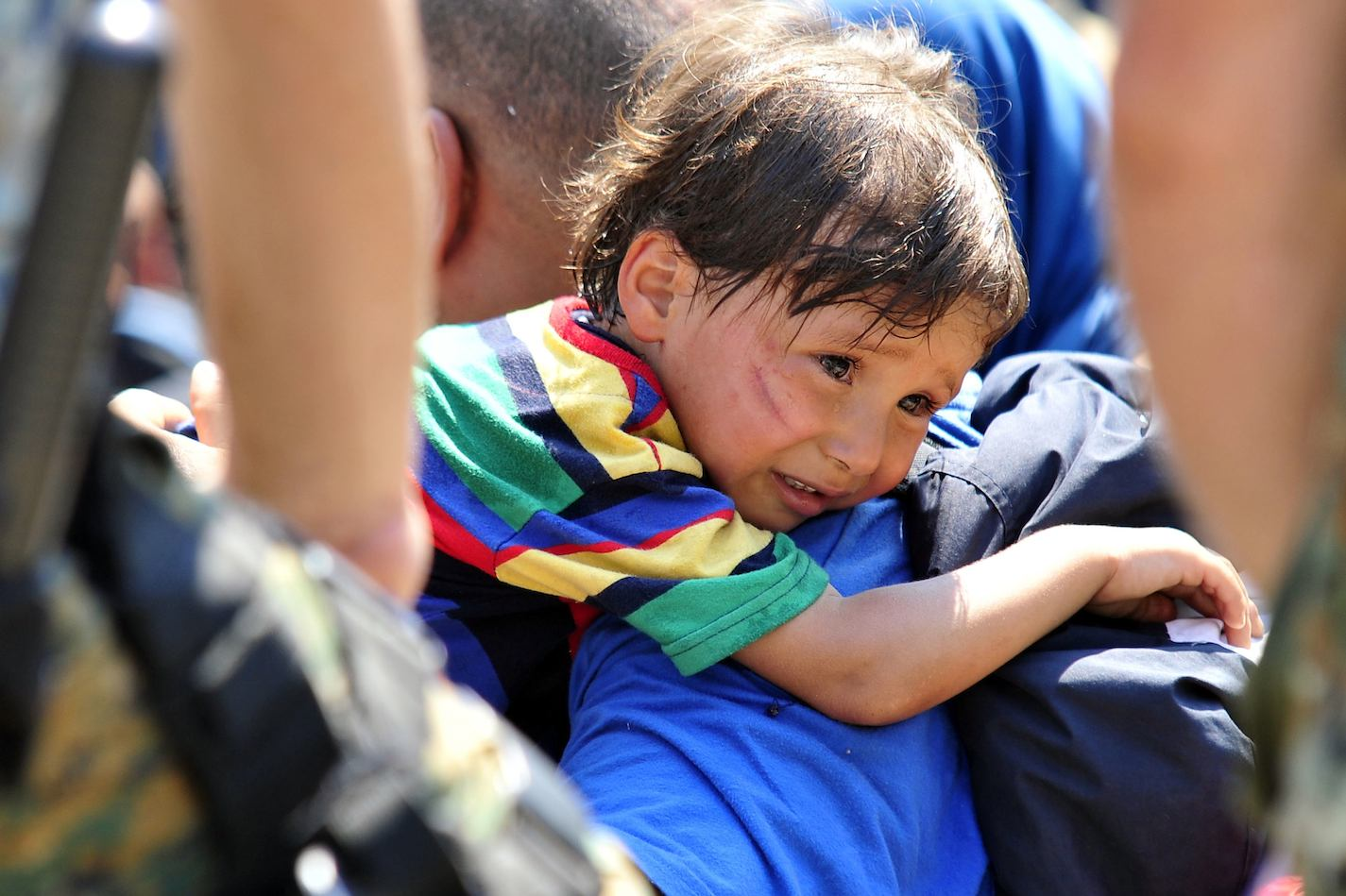 On 26 August, a distressed migrant child rests over a shoulder in a Macedonian town on the border with Greece.
